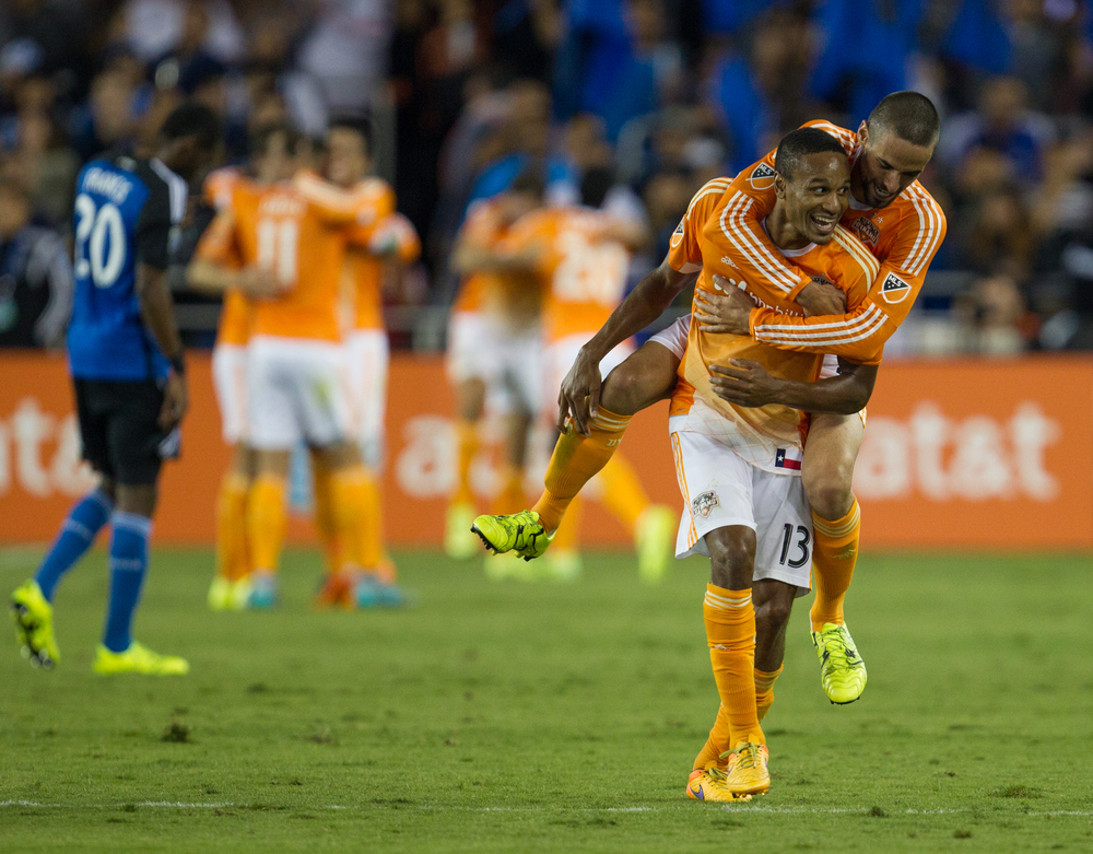 Dynamo defender RaúlRodríguez jumps on the back of teammate Ricardo Clark while celebrating a goal during a game between the San Jose Earthquakesand Houston Dynamo at Avaya Stadium in San Jose,California, on Friday, July 10, 2015.
