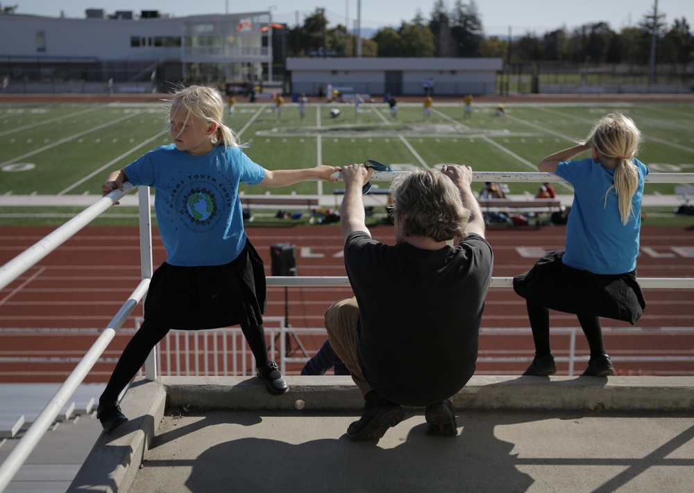 """Michael Read (center) hangs in the bleachers with daughters Sylvia Read (left), 7, and Malena Read (right), 9, before an ultimate frisbee game between the San Francisco FlameThrowers and San Jose Spiders at Laney College Football Field in Oakland, CA, on Saturday, July 18, 2015. The teams play in the """"American Ultimate Disc League""""."""