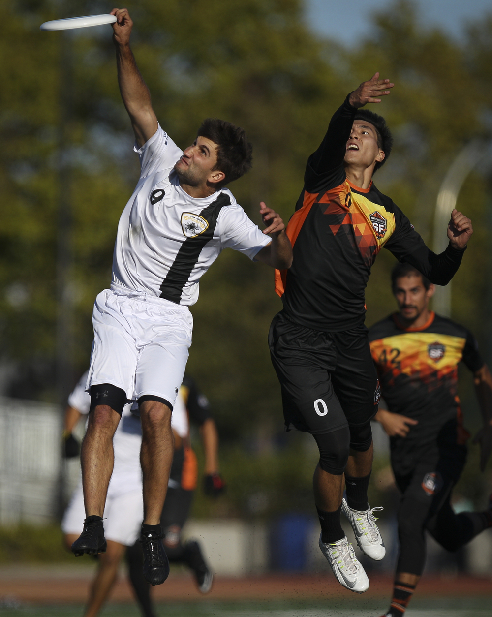San Jose Spiders player Cassidy Rasmussen (in white) snatches a throw as San Francisco FlameThrowers player Jason Yun contests during an ultimate frisbee game at Laney College Football Field in Oakland, CA, on Saturday, July 18, 2015.
