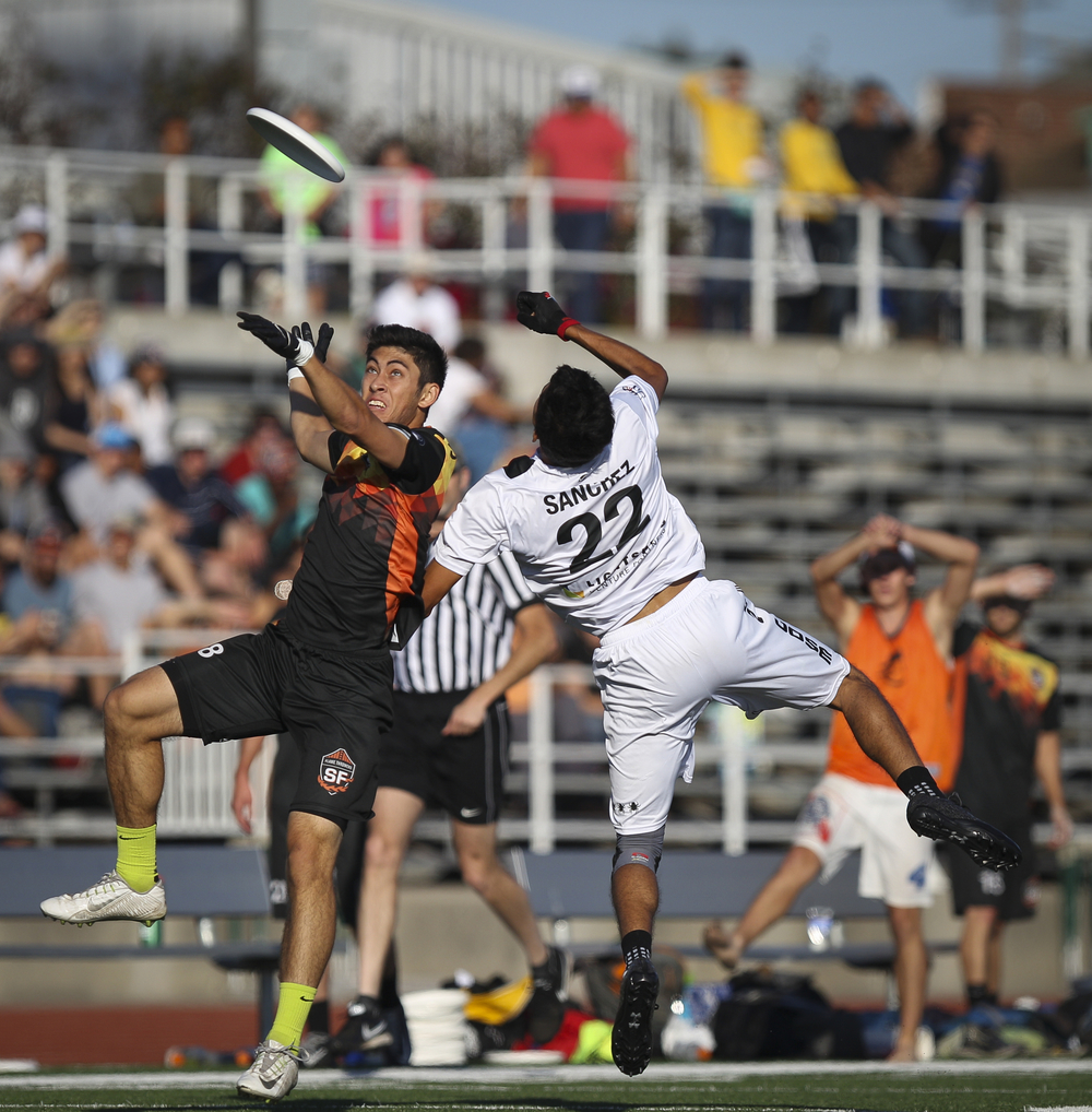 San Francisco FlameThrowers player Kohji Sugioka (in black) elevates for a pass as San Jose Spiders player Marcelo Sanchez contests during an ultimate frisbee game at Laney College Football Field in Oakland, CA, on Saturday, July 18, 2015.