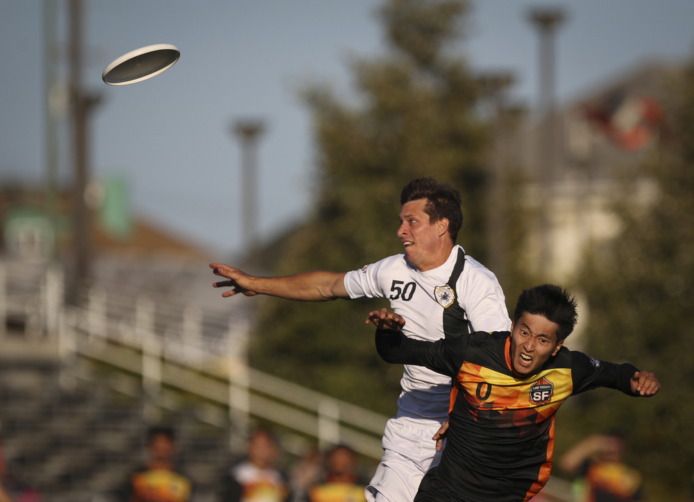 San Jose Spiders player Beau Kittredge (in white) leaps for a throw against San Francisco FlameThrowers player Jason Yun during an ultimate frisbee game at Laney College Football Field in Oakland, CA, on Saturday, July 18, 2015.