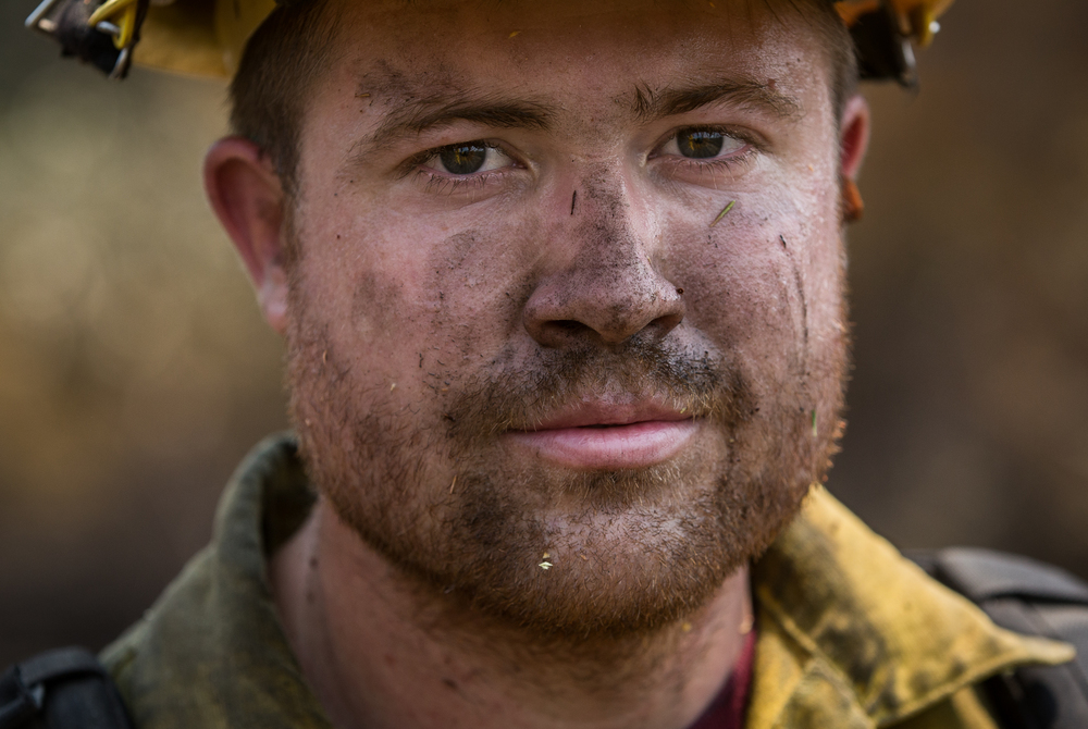 Firefighter Cody Morris is seen while taking a short break from tying together fire lines as mop-up duty along Morgan Valley Road near Lower Lake, Calif., on Saturday, Aug. 1, 2015. By clearing brush, highly-flammable areas can be contained. Morris' strike crew traveled to the Rocky Fire from headquarters at the Salyer Forest Service Guard Station in Salyer, Calif.