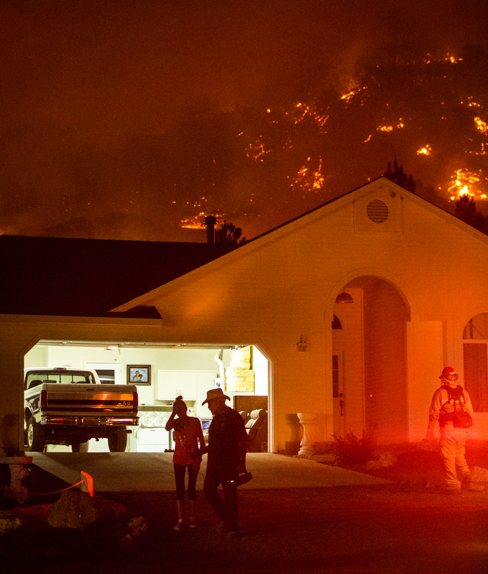 Mary Klemish and Bill Mederios leave Klemish's home on Morgan Valley Road near Lower Lake, Calif.,while being evacuated by firefightersWednesday, July 29, 2015. The Rocky Fire burned to within yards of the home, but it survived the night's blaze.