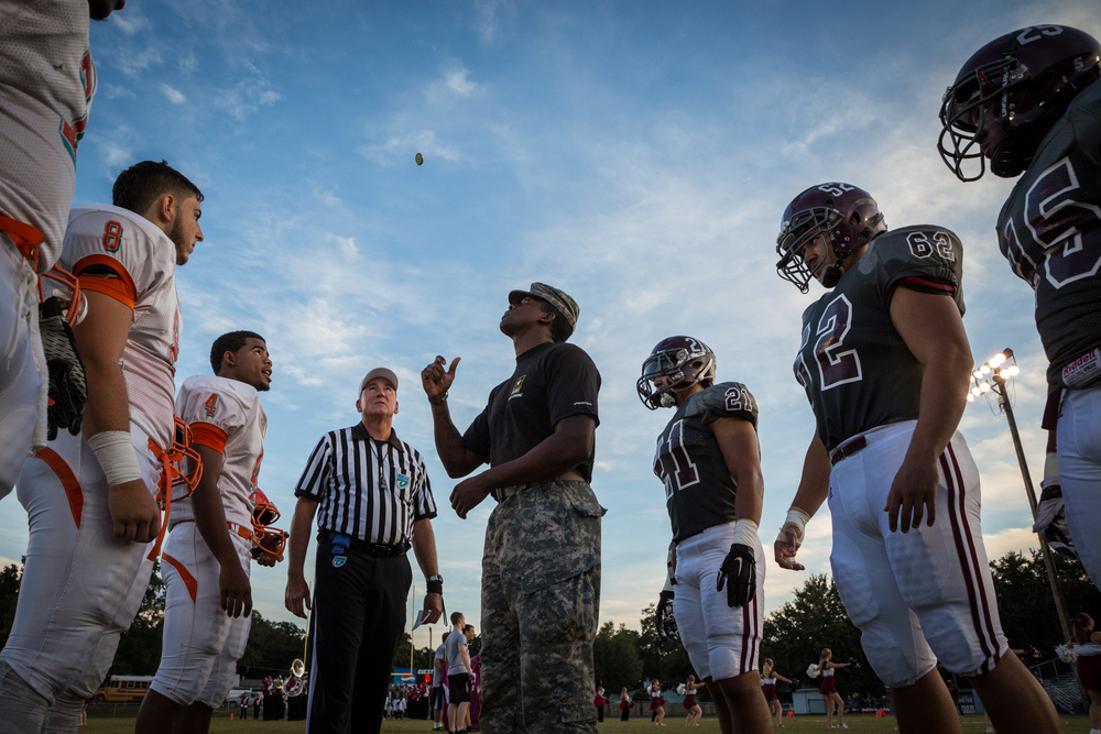Staff Sergeant Henry Hunt performs the coin toss before kick-off between Brandon High (right) and Plant City High in Brandon, Fla., on Friday, Sept. 11, 2015.