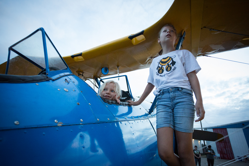 From left: Kristina Carver, 7, and sister Jessica Carver, 9, watch from their father's 1942 Boeing Stearman airplane as hot air balloons are inflated during the Festival of Flight at Tampa North Flight Center in Lutz, Fla., on Sunday, Sept. 13, 2015. Their father, Keith Carver, took festival attendees up in the Stearman for $75 per flight following the balloon show.
