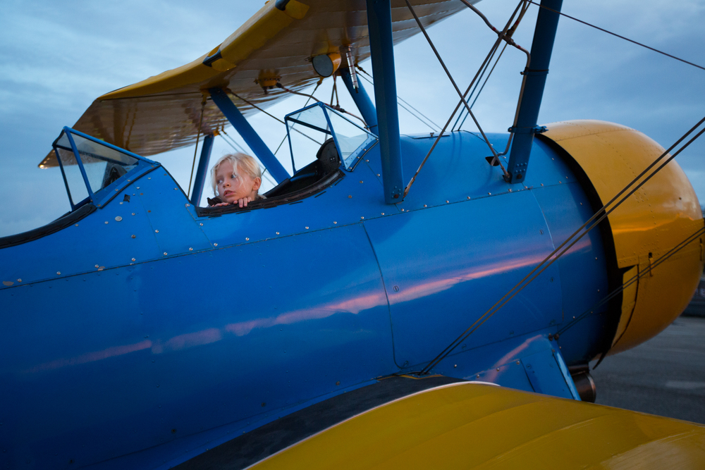 Kristina Carver, 7, watches from her father's 1942 Boeing Stearman airplane as hot air balloons are inflated during the Festival of Flight at Tampa North Flight Center in Lutz, Fla., on Sunday, Sept. 13, 2015. Carver's father, Keith Carver, took festival attendees up in the Stearman for $75 per flight following the balloon show.