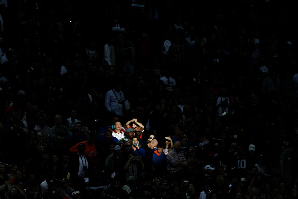 Fans are illuminated in a spot of light at the SEC championship game between the Florida Gators and Alabama Crimson Tide at the Georgia Dome in Atlanta, Ga., on Saturday, Dec. 5, 2015.
