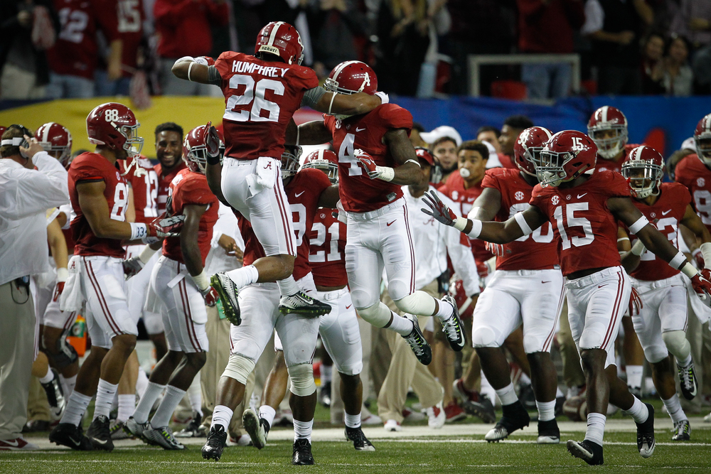 Alabama Crimson Tide defensive back Marlon Humphrey (26) celebrates with teammates after intercepting a pass from Florida Gators quarterback Treon Harris (3) in the third quarter of the SEC championship game between the Florida Gators and Alabama Crimson Tide at the Georgia Dome in Atlanta, Ga., on Saturday, Dec. 5, 2015.