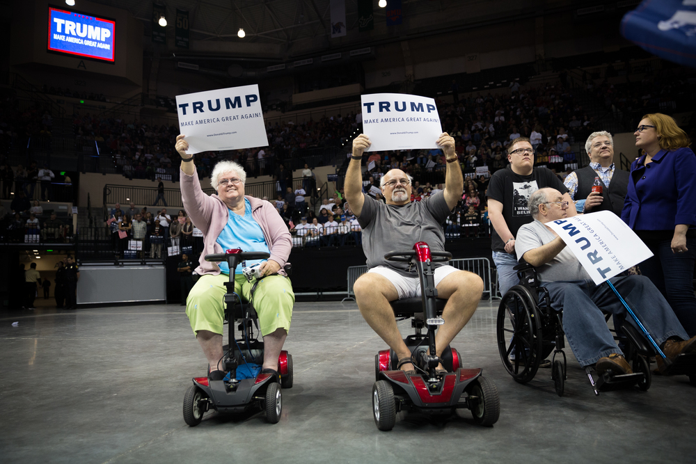 Lillian Cameron (left) and husband Irving Cameron (center) hold up signs at a Donald Trump rally during the business mogul's presidential campaign at the University of South Florida Sun Dome in Tampa, Fla., on Friday, Feb. 12, 2016. The couple made the trip from Spring Hill to show their support.