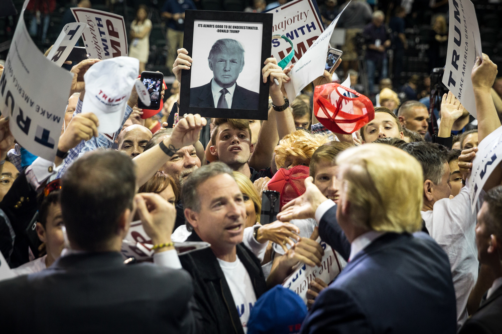 Donald Trump reaches out to shake the hand of a fan after finishing his speech at a rally during his presidential campaign at the University of South Florida Sun Dome in Tampa, Fla., on Friday, Feb. 12, 2016.