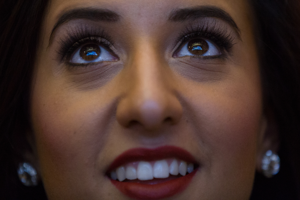 The big screen is reflected in the eyes of Tampa Bay Buccaneers cheerleader Tessa Pino-Slinn as she watches in anticipation of her team's first round selection.