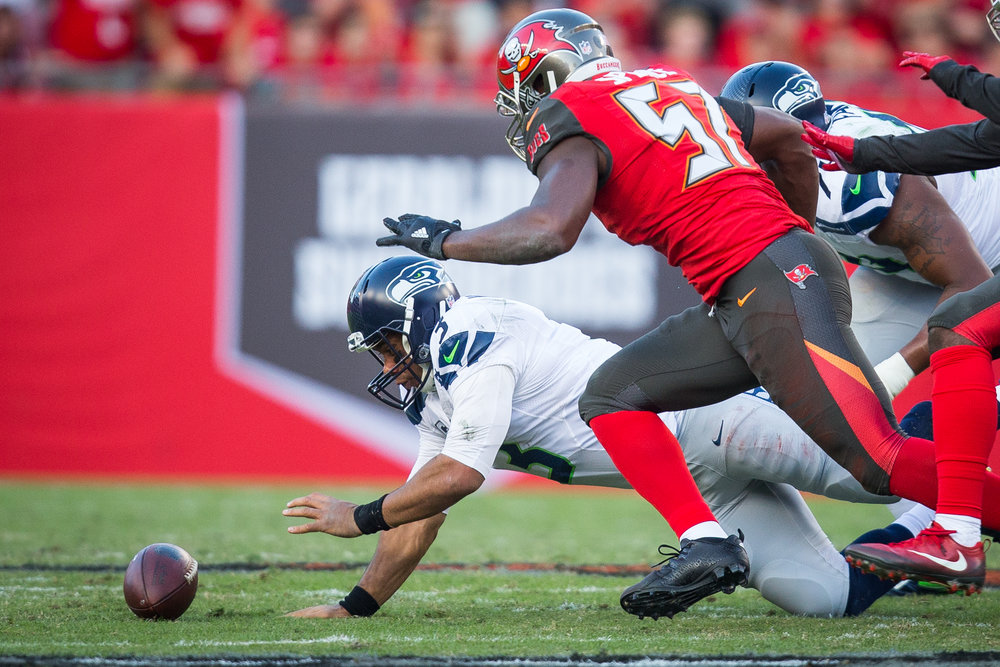 Seattle Seahawks quarterback Russell Wilson (3) dives on his own fumble while being sacked by Tampa Bay Buccaneers defensive end Noah Spence (57) during the first half of a football game at Raymond James Stadium in Tampa, Fla., on Sunday, Nov. 27, 2016.