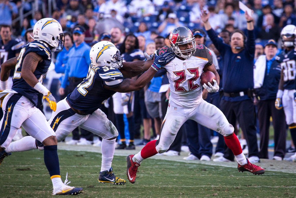 Tampa Bay Buccaneers running back Doug Martin (22) stiff-arms San Diego Chargers inside linebacker Denzel Perryman (52) on a run play during the second half of a football game at Qualcomm Stadium in San Diego, Calif., on Sunday, Dec. 4, 2016.