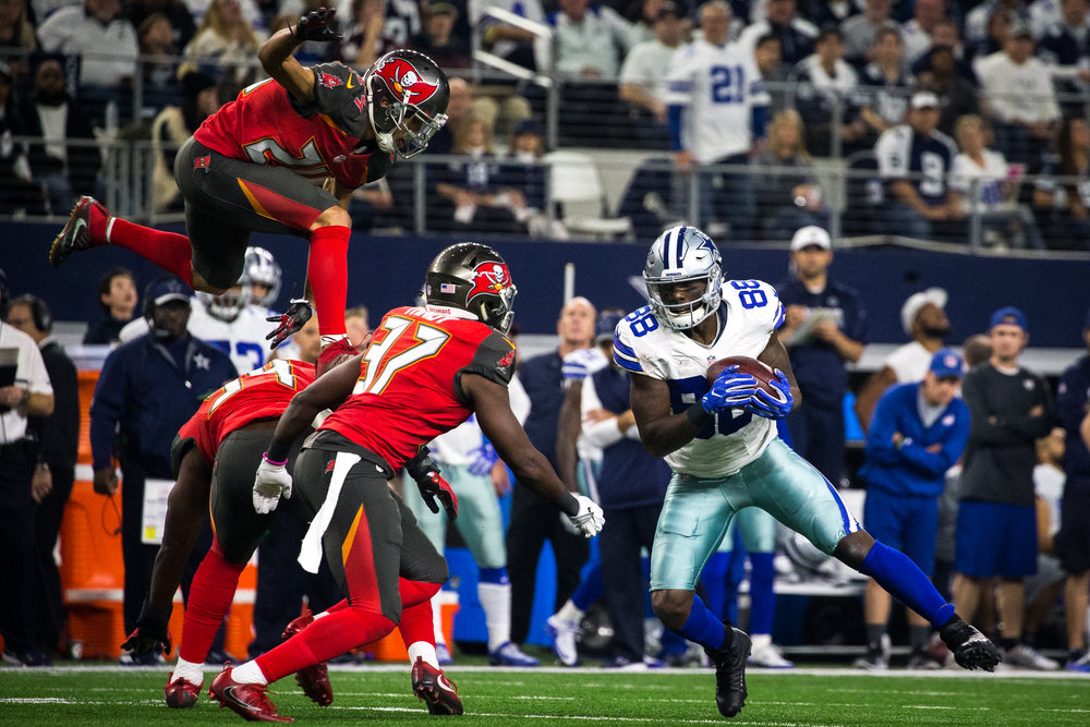 Tampa Bay Buccaneers cornerback Brent Grimes (24) flies through the air in an attempt to tackle Dallas Cowboys wide receiver Dez Bryant (88) after a reception during the first half of a football game at AT&T Stadium in Arlington, Texas, on Sunday, Dec. 18, 2016.