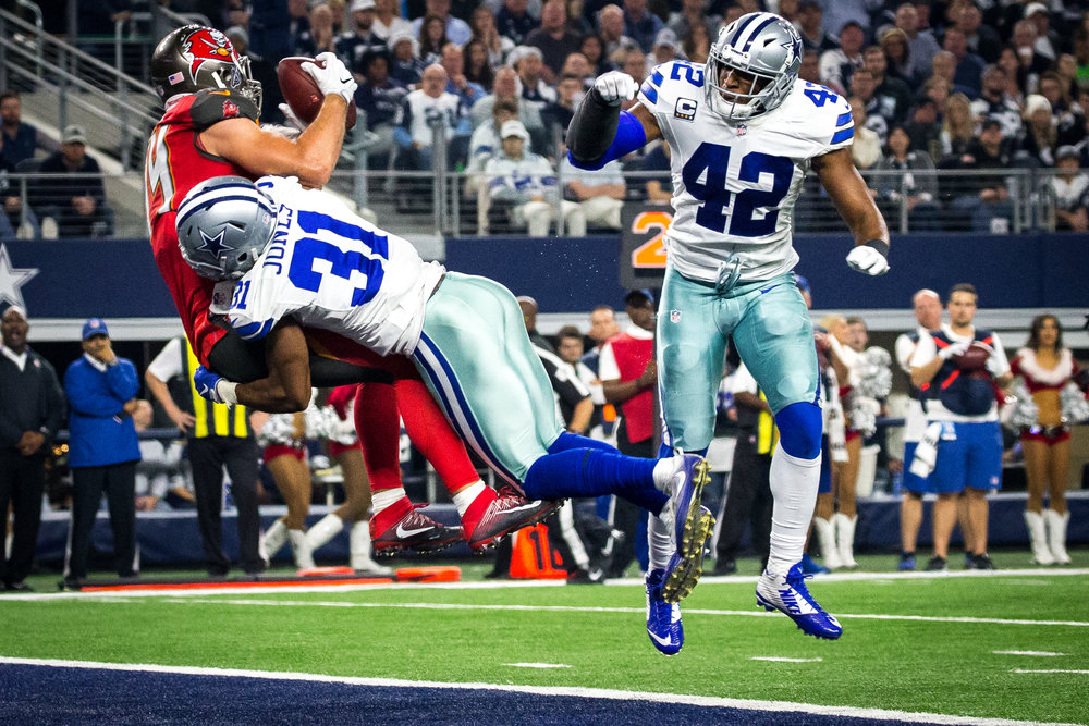 Tampa Bay Buccaneers tight end Cameron Brate (84) makes a touchdown catch as he's hit by Dallas Cowboys free safety Byron Jones (31) during the second half of a football game at AT&T Stadium in Arlington, Texas, on Sunday, Dec. 18, 2016.