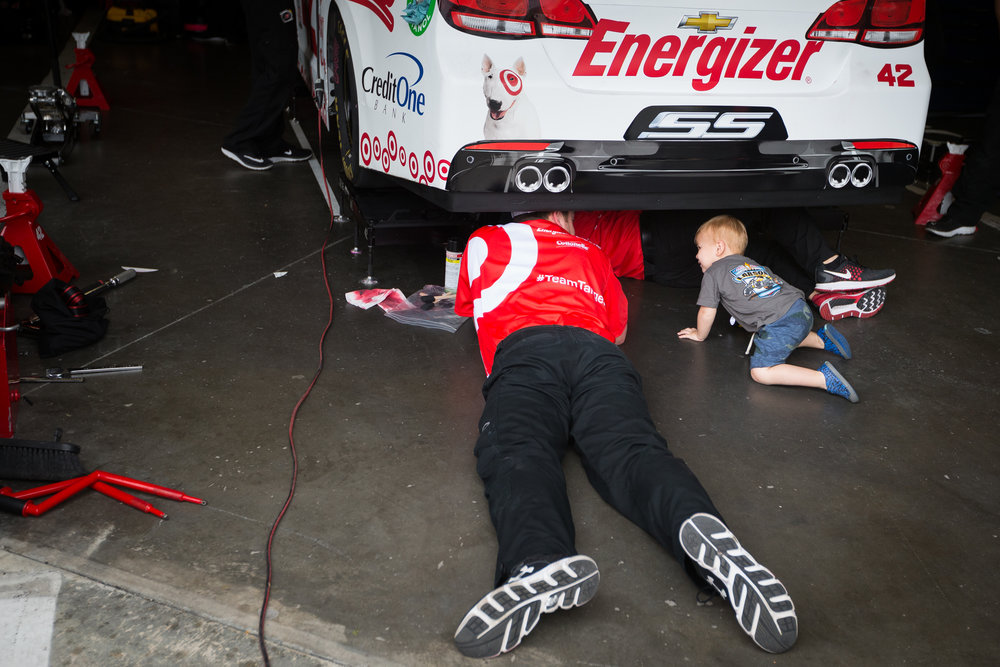 Owen Larson, son of driver Kyle Larson, tries to help out under his dad's car at Daytona International Speedway in Daytona Beach, Fla., on Saturday, Feb. 25, 2017.