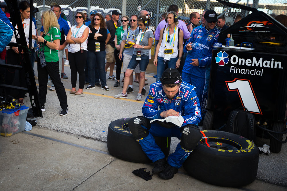 A member of Elliott Sadler's OneMain Financial Chevrolet crew reads the bible between pit spots during the NASCAR XFINITY series PowerShares QQQ 300 race at Daytona International Speedway in Daytona Beach, Fla., on Saturday, Feb. 25, 2017.