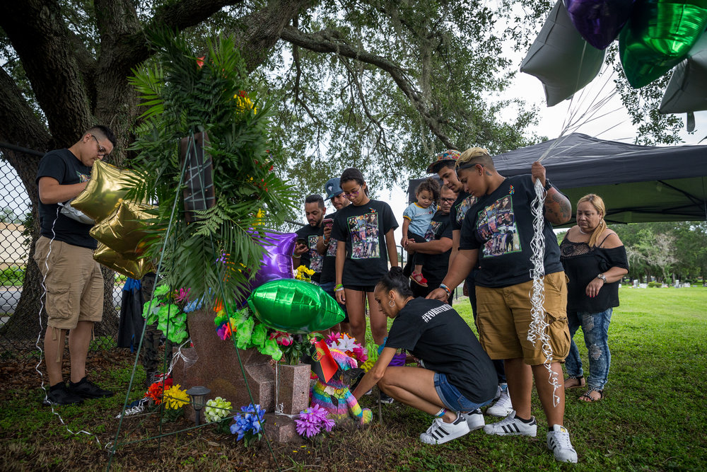 Loved ones of Leroy Valentin Fernandez, one of the victims of the Pulse nightclub shooting, celebrate his life at his grave at Greenwood Cemetery in Orlando, Fla., on Monday, June 12, 2017. This day marked the one-year anniversary of the attack.