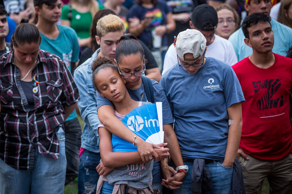 Vanessa Morales (right) holds hands with partner Aixa Soltren, who is seen embracing their daughter Alexis Guzman, 11, during a vigil at Lake Eola honoring the 49 lives lost exactly one year earlier in a mass shooting inside Pulse, a gay nightclub, in Orlando, Fla., on Monday, June 12, 2017. Soltren was at Pulse the night of the attack, but departed before the shooting began.