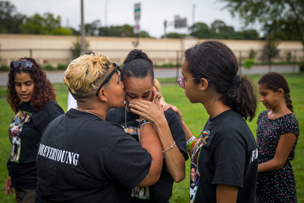 Carla Montanez (center) is consoled by girlfriend Angel Ayala (left) and daughter Keila Murillo while grieving the loss of friend Leroy Valentin Fernandez on the one-year anniversary of the Pulse shooting, at Greenwood Cemetery in Orlando, Fla., on Monday, June 12, 2017. At Fernandez's grave, they danced to a Beyoncé song that brought back fond memories and left balloons.