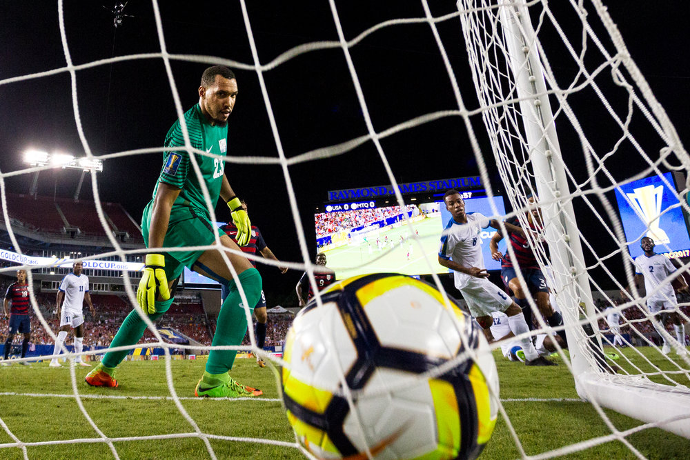 Martinique goalkeeper Kévin Olimpa watches a United States' Omar Gonzalez goal hit the back of the net during the second half of a CONCACAF Gold Cup soccer match.
