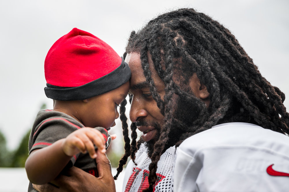 Tampa Bay Buccaneers defensive back J.J. Wilcox (27) holds son James Wilcox III, 7 months, after practice at training camp at One Buccaneer Place in Tampa, Fla., on Monday, July 31, 2017.
