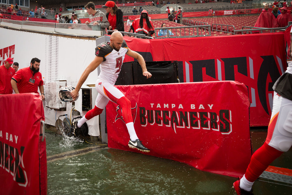 Tampa Bay Buccaneers punter Bryan Anger (9) jumps through a growing puddle before a preseason game between against the Cleveland Browns. The game included two weather delays.