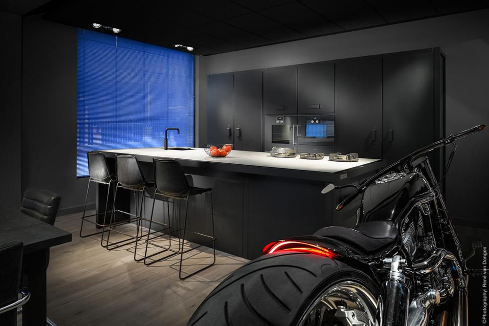 bachelor-kitchen-roaring-motorbike-blue-screen-wndow-black-cabinetry.png