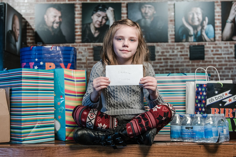 "Izy with the many items she bought for the homeless and a 'love letter' to her favorite homeless friend, Caveman - in the background are portraits of the homeless from the project ""The Road I Call Home"" and Caveman is the man on the far left laughing."
