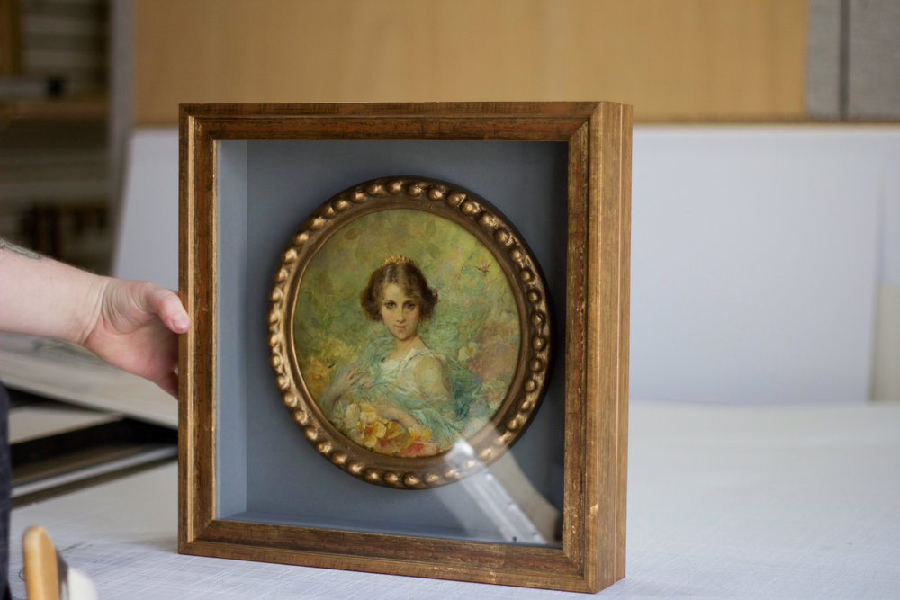 The art secure within a shadowbox frame.