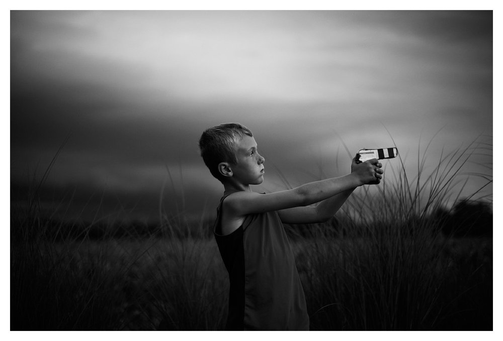 The third image I submitted that didn't get picked. I LOVE this image and I mean LOVE. It shows my son in his element better than most photos I have of him. I love the fact that there was a storm rolling through and the atmosphere feels a little electric to me. The cardboard and electrical tape gun makes me laugh and shake my head a bit and his serious as a heart attack expression on his face, well, I love it. I also love that his hair is really blonde from all the sun from the summer....the big bug bite on his arm tells me how much time he spent outdoors, enjoying life. That fact that this photo didn't get picked doesn't mean anything to me other than maybe it didn't go well with how Rodney wanted to curate his picks. Maybe he doesn't like guns. Maybe he doesn't like photos of kids.....there are a million, zillion maybes, but none of these reasons should make me upset, offended or rejected.