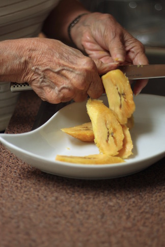 Abuela slicing sweet plantains