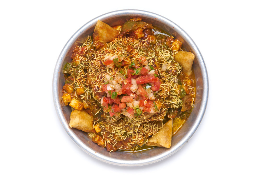 DECONSTRUCTED SAMOSA an inside out phenomenon loaded with chana, pico kachumber, chutneys, crispy sev noodles, mini samosas choice of chicken, paneer, aloo gobi or lamb or vegan chicken