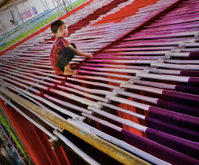 Child working in textile industry.   Photo courtesy of The Guardian  .
