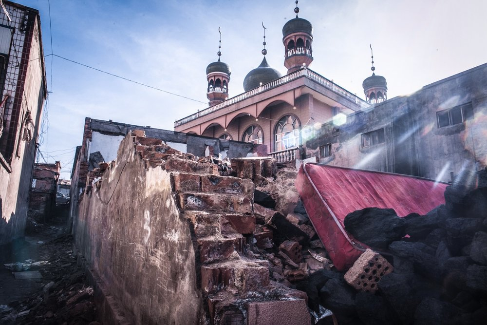 The rubble of Uyghur migrant housing surrounds a neighborhood mosque.