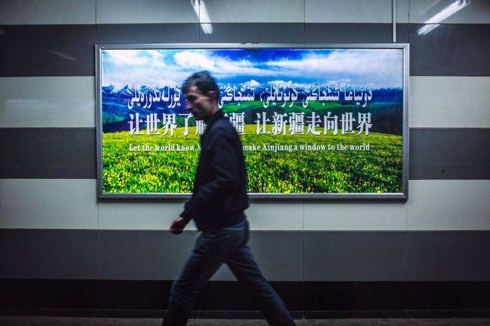 A Uyghur young man walks by a government sponsored sign promoting Xinjiang economic development.
