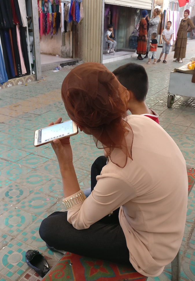 A woman who owns a woman's clothing shop in a rural bazaar sits listens to the messages of a WeChat group.