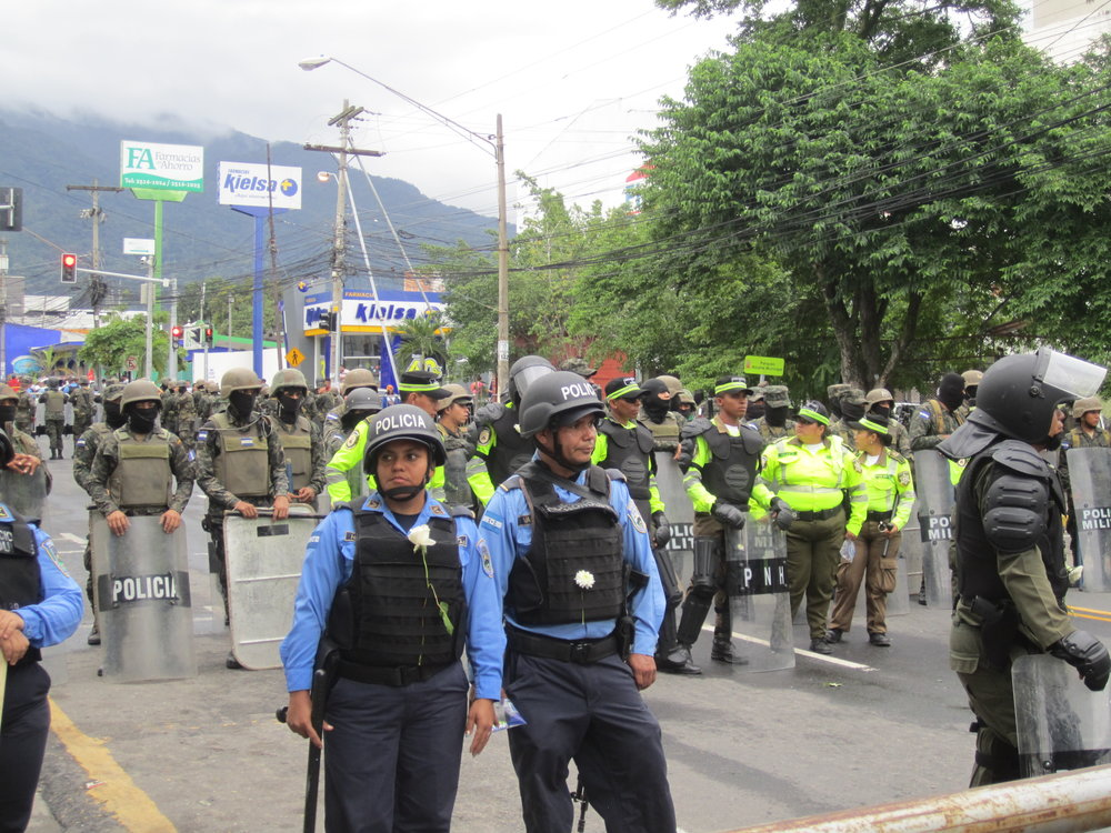 San Pedro Sula, Cortés. Sunday, December 3rd. Military and police stand ready while a peaceful protest is underway. Protestors gave white flowers to the police officers. Photo credits: Author.