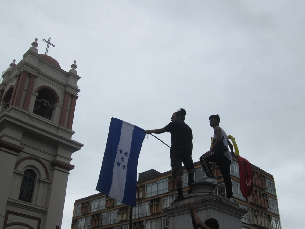 San Pedro Sula, Cort  é  s. Sunday December 3rd. Two protestors stand on the pedestal where a monument to the founder of the National Party once stood in San Pedro Sula  '  s central park.   Photo credits: Author.
