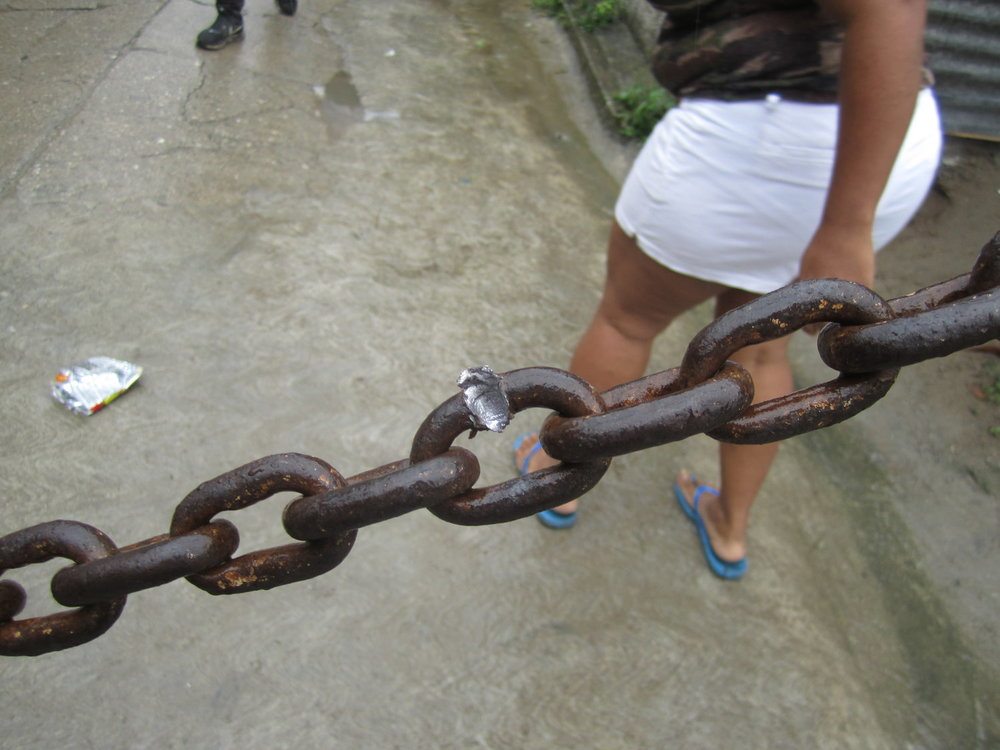 Sector López Arellano, Choloma, Cortés. Viernes, 1 de diciembre. La evidencia de donde una bala pegó una cadena en la entrada del barrio. Foto crédito: autora.