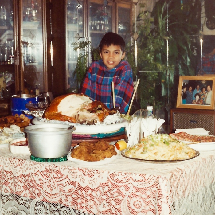 Chef Tom Cunanan as a young man, at a family party buffet spread. Note the iconic lace tablecloth. Photo credit: Bad Saint, Kickstarter.