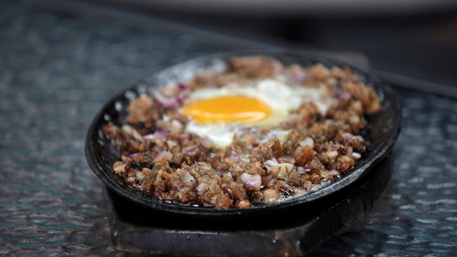 "Sisig, a Filipino dish, is pictured at a restaurant in Manila, Philippines on July 28, 2017. Anthony Bourdain told CNN Philippines in 2017 that Filipinos in the US ""maybe underrated their own food,"" and said that  sisig  would be the break-out dish.  Credit: Dondi Tawatao/Reuters"