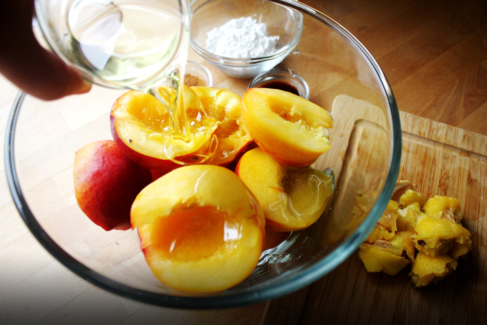 Coat the halved and pitted peaches in vegetable oil.