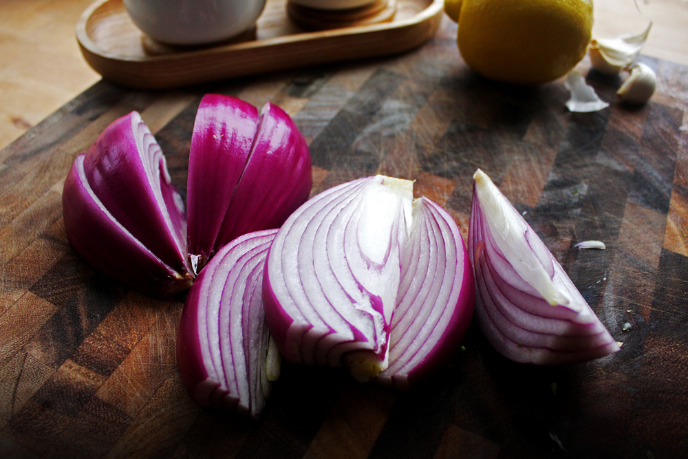 Peel and cut your onion in half, then quarter the half. Try to keep the root end intact as much as possible so the onion pieces don't fall through the grates.