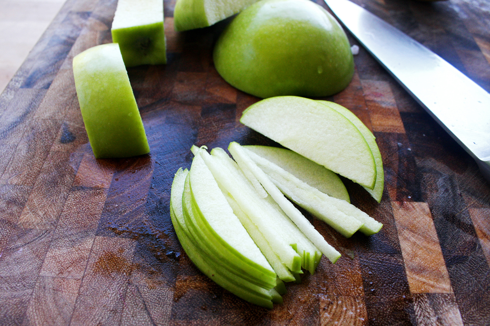 Cut the green apple into matchsticks, by thinly slicing the larger pieces vertically, then turning the pieces to the side and slicing into the matchstick shape.