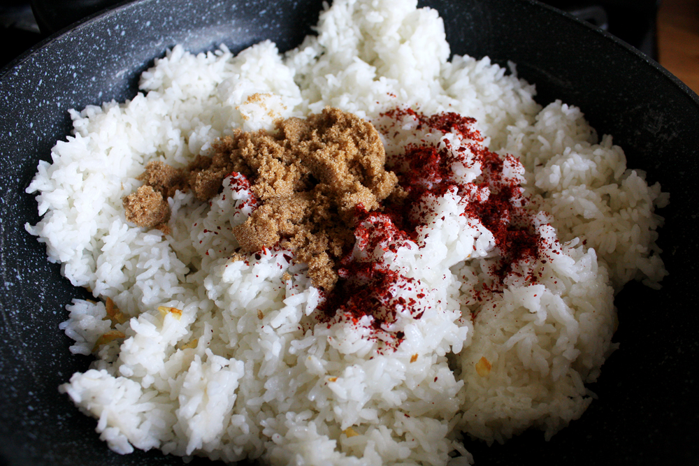 Add in your rice, brown sugar and gochugaru. By the way, this dish is perfect with old cooked rice you have laying around. I've made this with a fresh batch, and just let it cool to room temperature and it was still delicious.