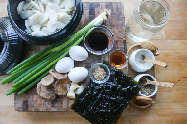 The ingredients: sliced rice cakes, green onions, garlic, soy sauce, dried shiitake mushrooms, eggs, sesame seed oil, sesame seeds, roasted seaweed, salt, pepper and water.