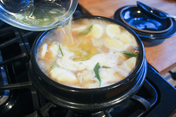 When the broth is ready, discard the mushrooms (you can totally leave them in, the vegetarian husband just doesn't like them so I toss 'em) and add in the rice cakes and the reserved top parts of the green onion. Continue boiling for about 5 more minutes, the rice cakes should be floating, then turn off the heat and immediately add in the egg whites, stirring only once to get larger pieces to form.