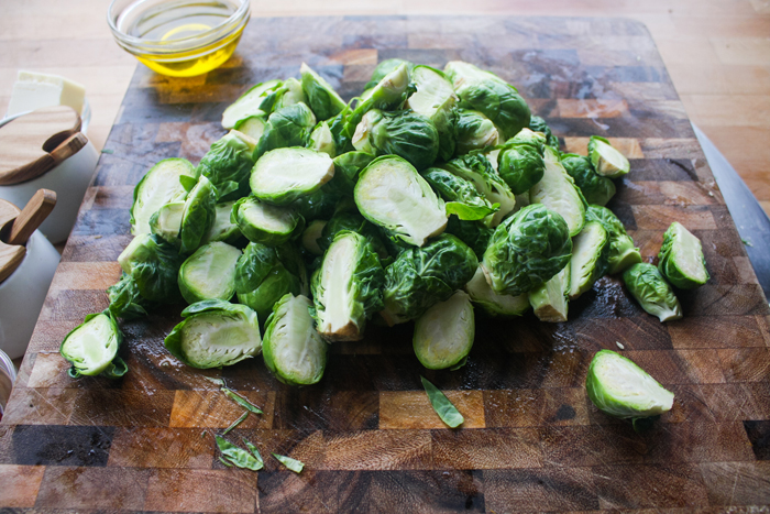 Cut off any tough woody ends, then cut the brussel sprout in half.