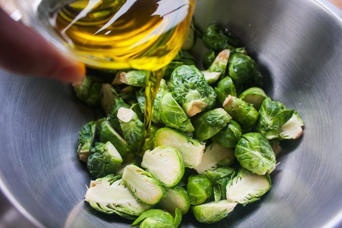 Coat with olive oil. You want to do this on the sprouts before putting in the pan so that every piece can get some nice charring, and it wont be so smokey.